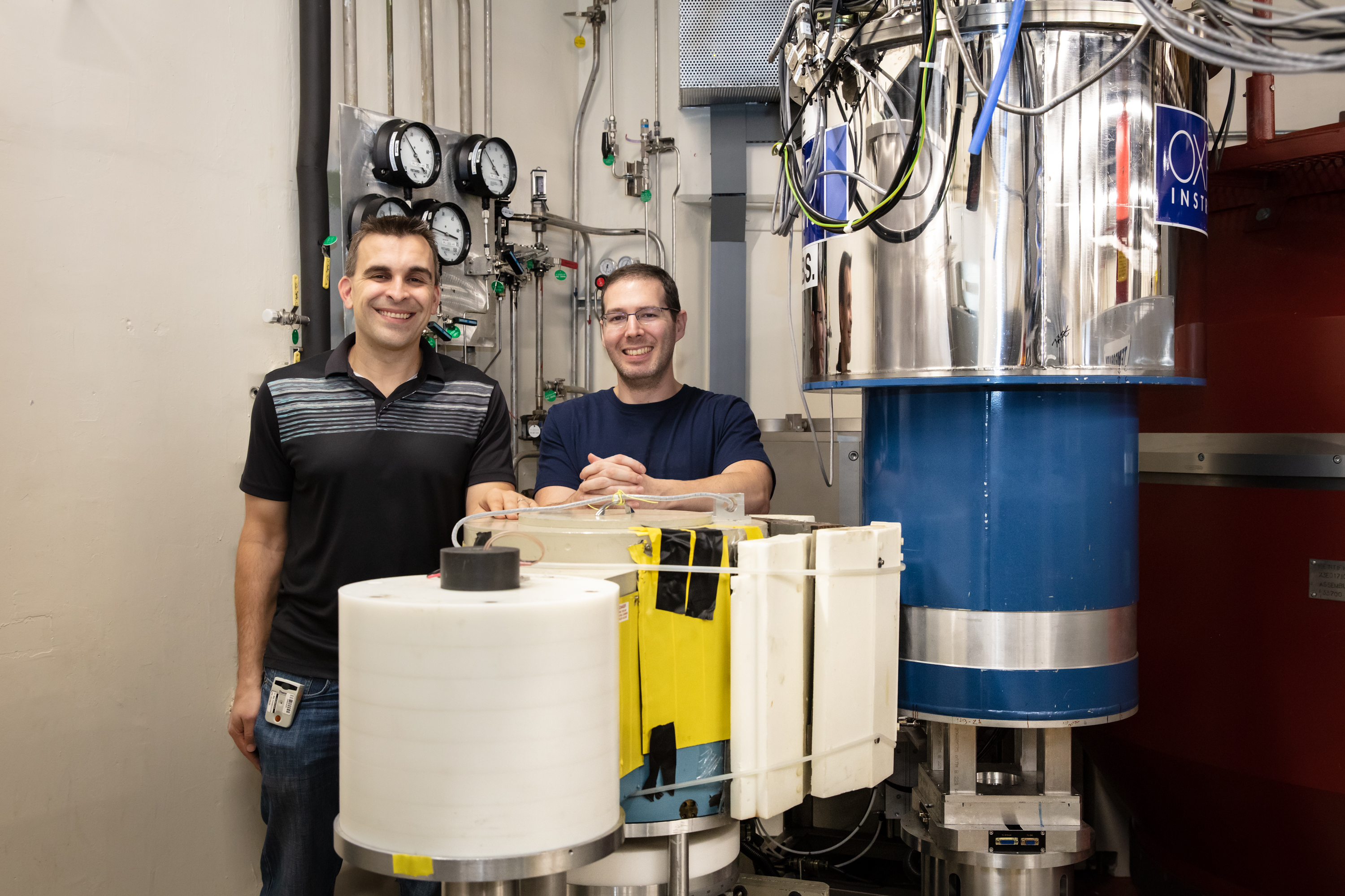 ORNL scientists Adam Aczel and Gabriele Sala stand beside the High Flux Isotope Reactor's FIE-TAX instrument. Ross and her team used FIE-TAX to explore ytterbium silicate's microstructure and find evidence for a BEC phase. (Credit: ORNL/Genevieve Martin)