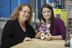 ORNL's Bianca Haberl and Amy Elliott hold 3D printed collimators next to a pressure cell loaded with a sample. These collimators were developed as a collaboration between the lab's Neutron Sciences Directorate and Manufacturing Demonstration Facility. (Image credit: ORNL/Genevieve Martin)