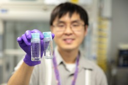 ORNL's Christopher Lam holds two samples of polymer gels, which have useful applications in medicine and consumer products. (Credit: ORNL/Genevieve Martin)