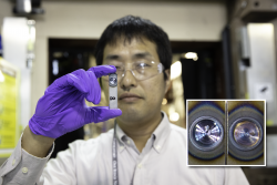"""Researcher Koichi Taniguchi from JFE Steel Corporation holds two pieces of the company's advanced high-strength steel held together by a friction stir spot weld. The welding process leaves a circular """"onion ring"""" pattern (inset photo) where the overlapping steel sheets are joined. CREDIT: ORNL/Genevieve Martin"""