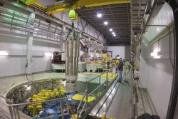 A heavy overhead crane is used to lower the 64,000-pound inner reflector plug into position, right in the heart of the Spallation Neutron Source. (image credit: ORNL/Genevieve Martin)