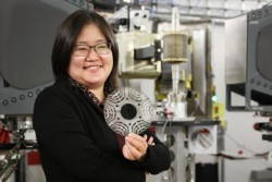 GE researcher Min Zou holds a metal laminate sheet made from a novel magnetic material used in a GE's prototype synchronous reluctance motor. Credit: ORNL/Genevieve Martin