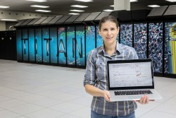 Ada Sedova, a postdoctoral research associate at the Oak Ridge Leadership Computing Facility (OLCF), develops computational calculations for supercomputing codes. In front of the OLCF's Titan supercomputer, Sedova displays a spectrum from her experimental work, measuring the vibrational frequency of nucleobases (bases of DNA and RNA) at the Spallation Neutron Source, and complementary computational calculations.