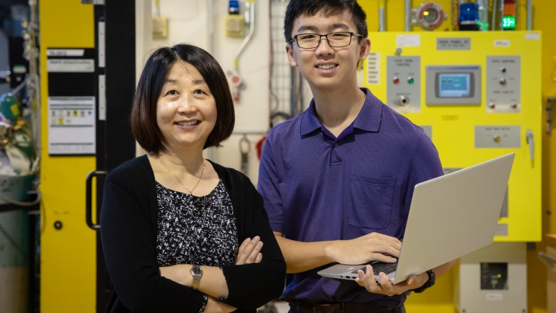 Corning Incorporated senior research scientist Ying Shi (left) uses neutron scattering to understand the structure–property correlation in glass to make new compositions. Her son, Albert Song (right), wrote data analysis code for her project and joined her on a recent visit to the Spallation Neutron Source. Credit: Genevieve Martin/Oak Ridge National Laboratory, U.S. Department of Energy.