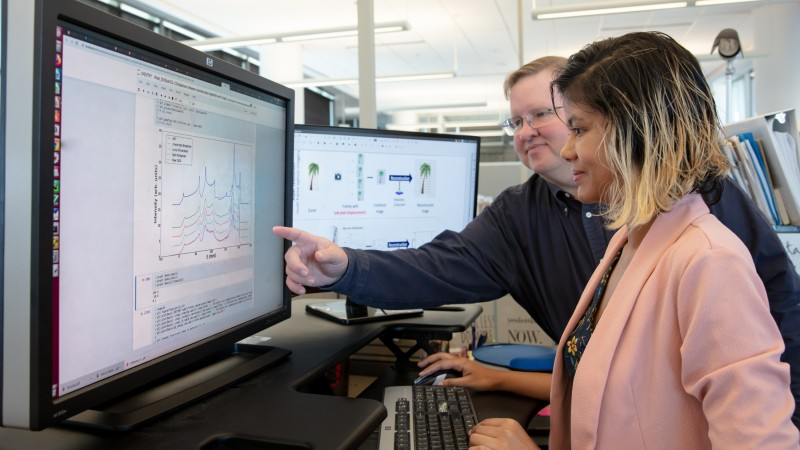 ORNL researchers Garrett Granroth and Fahima Islam observe data filtered through their new software, which gives researchers access to data with five times more resolution than traditional data reduction methods. (Credit: ORNL/Genevieve Martin)