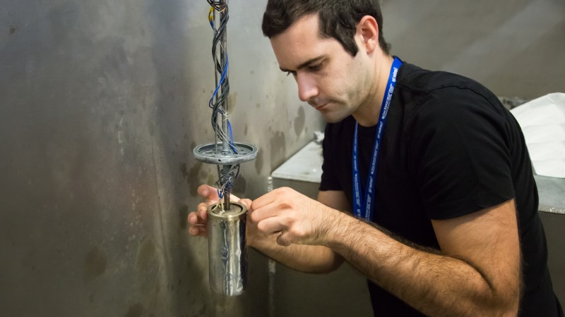University of South Carolina researcher Gregory Morrison prepares a SIM sample to be lowered into the neutron beam. This team is studying hierarchical structures for their applications in nuclear waste storage. Eventually, they hope to develop a new material for stabilizing and storing nuclear waste. (Image credit: ORNL/Genevieve Martin)
