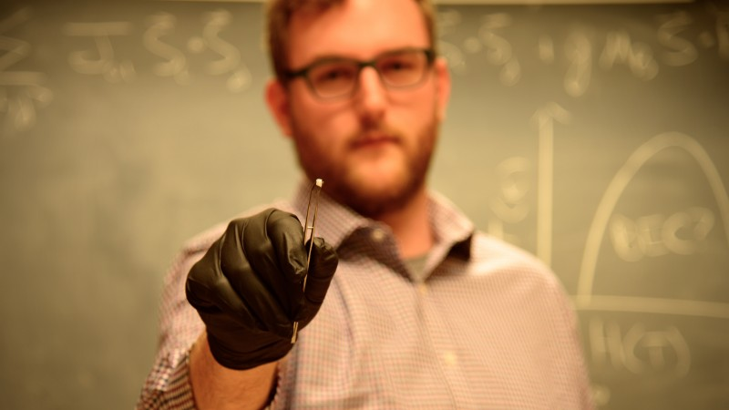 Colorado State University researcher Gavin Hester holds a sample of ytterbium silicate. He and his colleagues are using neutrons at Oak Ridge National Laboratory to study the material to better understand an unusual quantum phase called a Bose-Einstein condensate. (Credit: CSU/Daniel Shaw)
