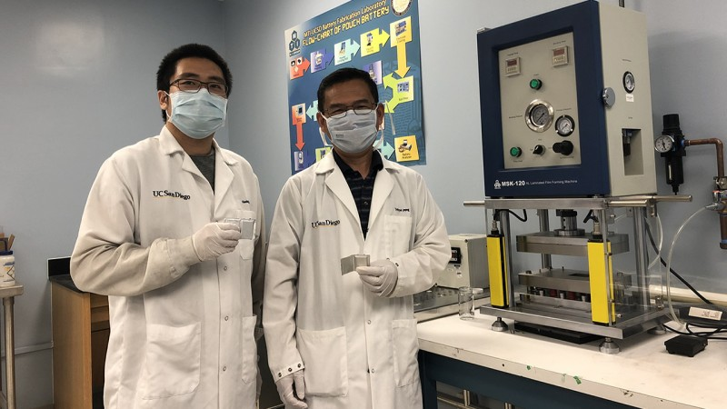 Researchers Haodong Liu and Ping Liu hold batteries made with the disordered rocksalt anode material they discovered, standing in front of a device used to fabricate battery pouch cells. (credit: UC San Diego)
