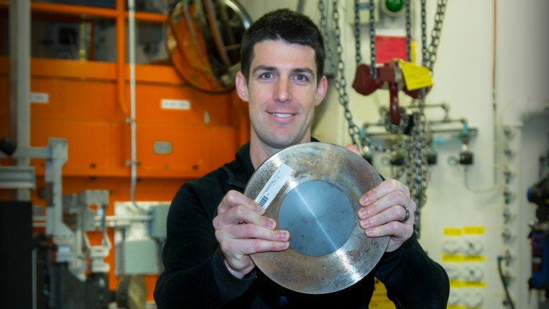Shannon Ryan, a researcher from the Australian Defence Science and Technology Group, is holding one of the twelve ceramic samples tested at HFIR's beam line for residual stress tests. The material is confined by a steel ring to apply the correct amount of pressure for testing via HB-2B's neutron mapping technology, which measures the strain distributed throughout the ceramic sample. Image credit: Genevieve Martin/ORNL.