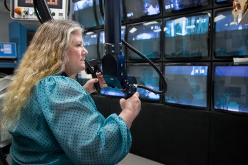 """Technical manager Linda Farr leads the remote handling team responsible for monitoring and replacing essential equipment for daily operations at Oak Ridge National Laboratory's Spallation Neutron Source. Robotic arms called """"servomanipulators"""" allow her to handle this equipment from a central control room. (Image credit: ORNL/ Genevieve Martin)"""