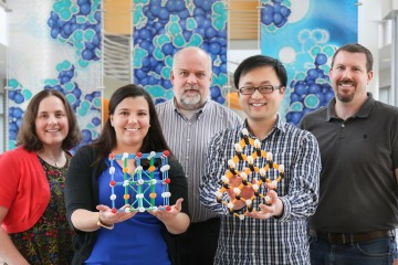 "Members of the ORNL NScD collaborated to create an invited ""poster"" with interactive elements for EMA2017. The 3-D display showcases research on the structure of nanocrystals. From left to right, the team includes Katharine Page, Tedi-Marie Usher-Ditzian, Thomas Proffen, Jue Liu, and Daniel Olds. (Image credit: ORNL/Genevieve Martin)"